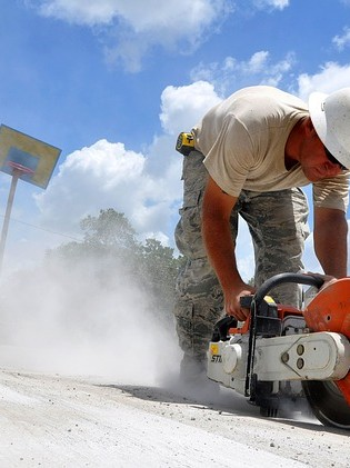 DC Dirt Work & Hydro-vac Services Concrete Cutting & Coring. Man in white hard hat cutting concrete with concrete saw.